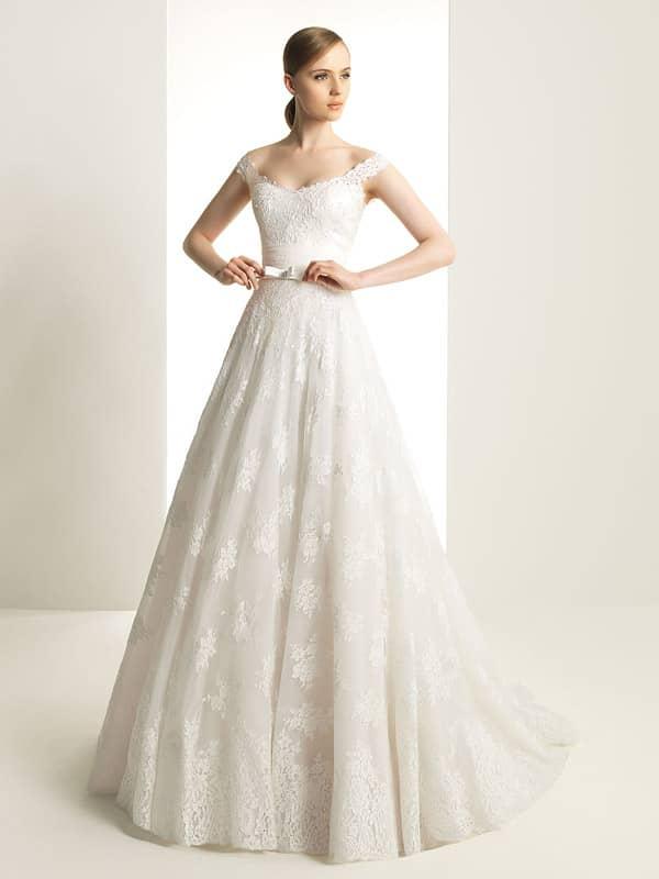 Кружевное свадебное платье с широким вырезом декольте и узким атласным поясом с бантом.