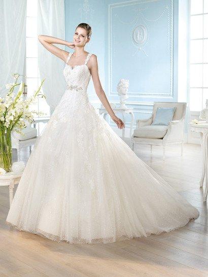 Красивое свадебное платье на бретелях силуэта «принцесса» со шлейфом известного испанского бренда St. Patrick из Pronovias Fashion Group.  Кружевной лиф, расшитый бисером, на бретелях, которые «держат» спинку с кружевной аппликацией на прозрачной основе.  Многослойная юбка, сплошь усыпанная «горошинками», декорирована слетающими к подолу фрагментами вышивки.  Талия подчёркнута поясом с крупной брошью по центру переда и бантиком сзади.