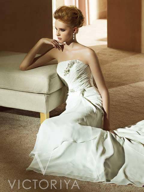 Дешевое свадебное платье смотрится элегантно благодаря прямому вырезу декольте и сдержанному силуэту.