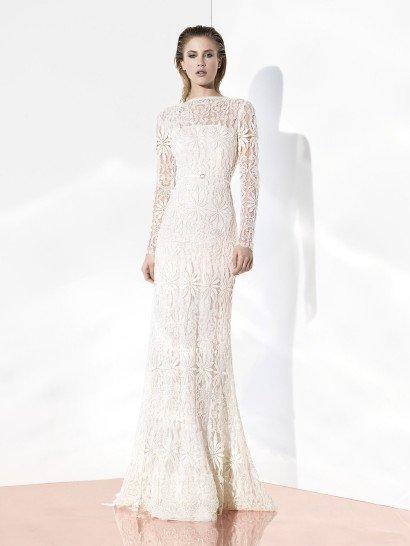 Эффектное облегающее свадебное платье на чехле линии «Glint Couture».  Эксклюзивное кружево с крупным симметричным рисунком в стиле «арт-деко» сплошь покрывает грациозный силуэт с высоким прямым вырезом горловины и длинными рукавами.  Талия акцентирована узким пояском.  Свадебные платья Yolan Crisэксклюзивно представлены в салоне Виктория  Примерка платьев Yolan Cris -платная