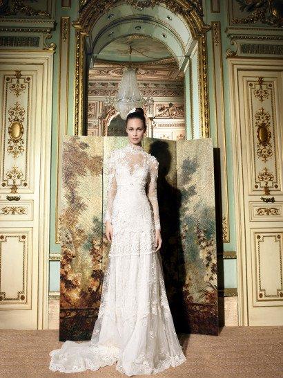 Роскошное прямое свадебное платье со шлейфом и длинными рукавами линии «Romantic Tale».  Область декольте с воротником «стойкой» и глубокий вырез спинки прикрыты прозрачным кружевом.  Плечи и рукава украшены ассиметричным авторским дизайном объёмного кружевного декора, нисходящими к подолу ажурными горизонтальными полосами.  Завышенная линия талии акцентирована узким пояском.  Свадебные платья Yolan Crisэксклюзивно представлены в салоне Виктория  Примерка платьев Yolan Cris -платная
