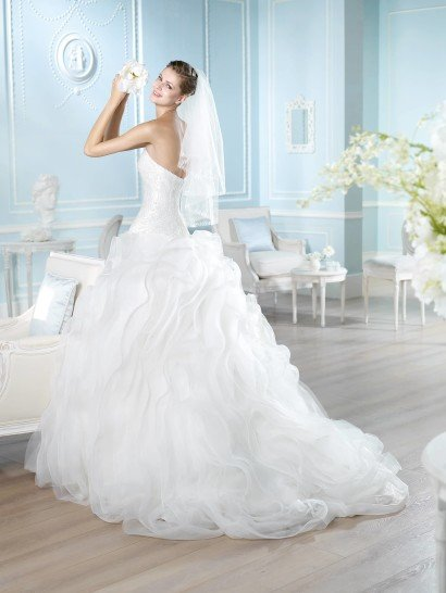 Впечатляющее свадебное платье с вышитым корсетом и торжественной пышной юбкой с оборками.