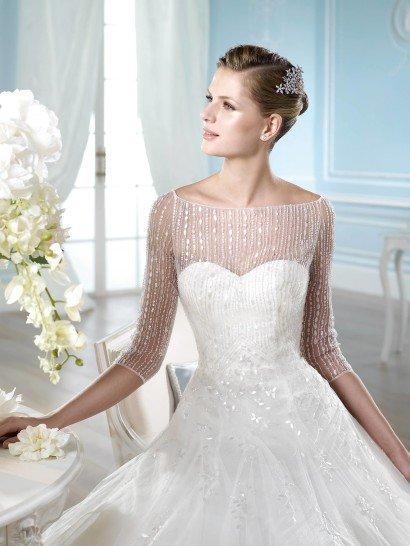 Свадебное платье с прозрачными рукавами и декольте.