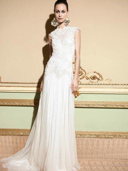Эксклюзивное свадебное платье линии «Romantic Tale».  Изысканная многослойная кружевная аппликация декорирует удлинённый лиф с высокой горловиной и рукавами «крылышками», формируя уникальную отделку категории «haute couture».  Плиссированная прозрачная сетка с узкими вертикальными кружевными полосами накрывает нижний слой шантильского кружева, создавая грациозный А-силуэт юбки со шлейфом.  Сзади – цепочка пуговиц.  Свадебные платья YolanCris эксклюзивно представлены в салоне Виктория