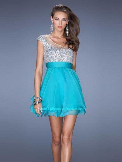 Потрясающее коктейльное платье с ассиметричным верхом привлекает внимание и насыщенной яркостью, и сиянием отделки.  Верх платья с одной бретелью полностью расшит блестящими пайетками. Его плавный изгиб элегантно оформлен полупрозрачной тканью с крупными сияющими камнями отделки.  Яркая лазурно-голубая юбка выполнена из нескольких слоев полупрозрачной ткани разной длины. Такой крой делает ее особенно красивой и летящей.  Это коктейльное платье не нуждается в лишней скромности, поэтому дополнить образ стоит крупными браслетами и серьгами.