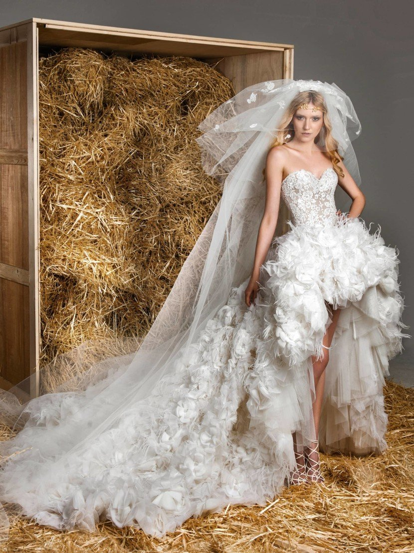 Эксцентричное свадебное платье с пышной юбкой, укороченной спереди и покрытой объемным декором.