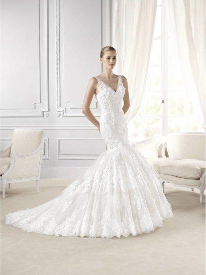 Свадебное платье силуэта «русалка» с V-образным вырезом элегантно подчеркивает изгибы женственной фигуры.  Тонкие бретели из полупрозрачной ткани повторяют форму декольте и на спинке свадебного платья, которую также украшает ряд декоративных пуговиц.  Корсаж отделан объемными цветочными аппликациями.  Юбка выполнена в два уровня, край каждого из которых декорирован широкой полосой кружевной ткани с цветочным мотивом.  Еще более торжественным образ становится благодаря шлейфу средней длины.
