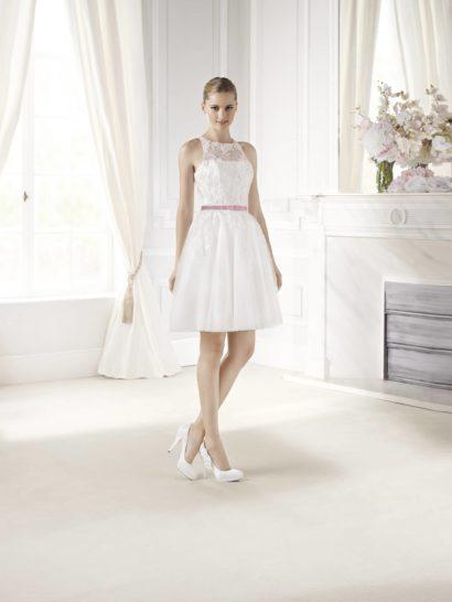 Короткое свадебное платье с пышной юбкой и оригинальной формой верха, открывающей плечи, идеально подойдет для создания непринужденного и романтичного образа.  Небольшой пояс привносит свежесть и служит отличным акцентом на талии.  Верх свадебного платья отделан аппликациями из кружева с цветочным мотивом.  Под полупрозрачной тканью – декольте с легким намеком на соблазнительный изгиб.  Юбка длиной чуть выше колена смотрится легкой и воздушной благодаря нескольким слоям матового фатина.