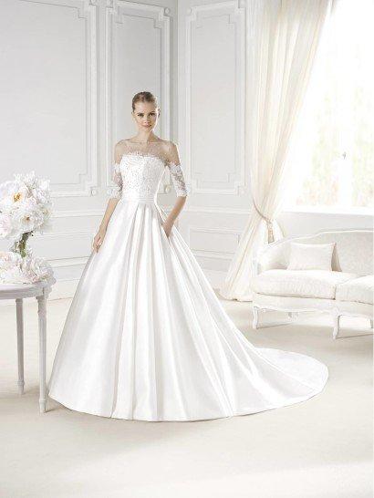Открытое свадебное платье с прямой линией декольте и А-силуэтом сочетает в себе торжественность сияющего атласа и романтичную сдержанность полупрозрачной кружевной ткани.  Оригинально оформленный верх плотным кружевом скрывает руки, а в области декольте о присутствии ткани говорит лишь изысканная отделка и легкий светлый оттенок.  Широкий пояс выгодно подчеркивает талию.  Объемная юбка со шлейфом из глянцевого атласа не нуждается в отделке – свадебное платье выглядит роскошно при всей лаконичности кроя.