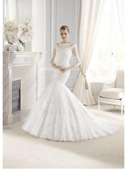 Элегантное свадебное платье для венчания силуэта «русалка» смотрится одновременно сдержанно и роскошно.  Впечатление подчеркивают и объемная юбка с внушительным шлейфом, и изысканная отделка, и крой верха.  Декольте сердечком скрыто полупрозрачной тканью, из которой сшит верх с воротником-лодочкой и рукавом длиной в три четверти.  Свадебное платье полностью расшито кружевами с цветочными и абстрактными мотивами, а на спинке его украшают декоративные пуговицы, длинный ряд которых идет от самого верха платья до линии бедра.