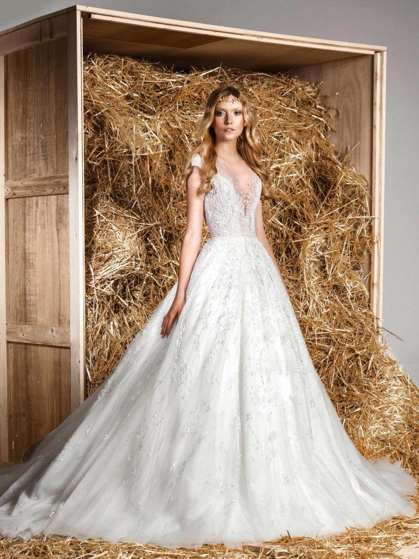 Торжественное свадебное платье с соблазнительным вырезом и многослойной юбкой со шлейфом.