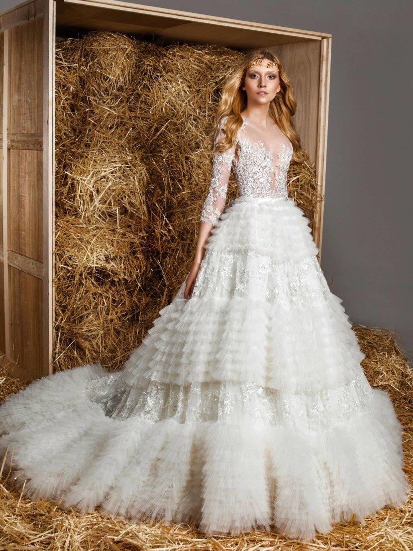 Драматичное свадебное платье с множеством горизонтальных оборок по пышной юбке.