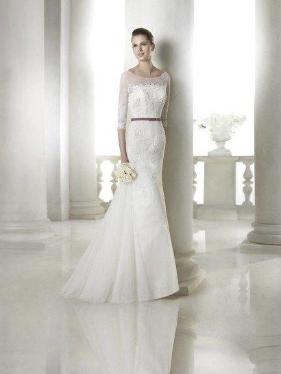 Элегантное недорогоесвадебное платье с прямым силуэтом идеально дополнено ярким поясом на талии, который при желании можно снять.  Насыщенный лиловый оттенок и лаконичный бант делают такой аксессуар очень стильным способом добавить в образ красок.  Верх платья с вырезом бато и длинные рукава оформлены тонкой ажурной тканью.  Кроме того, все свадебное платье за исключением воздушного фатинового шлейфа небольшой длины декорировано кружевными аппликациями с цветочным узором.  Свадебное платье из коллекции San Patrick