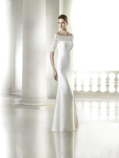 Элегантное недорогоесвадебное платье прямого силуэта из сияющего шелка демонстрирует все достоинства фигуры благодаря облегающему крою.  Прямое декольте скрыто кружевной тканью, из которой также сшиты рукава длиной до локтя.  Талия подчеркнута широким шелковым поясом.  Юбка в пол смотрится роскошно без всякой отделки.  Благодаря лаконичному декору, такое свадебное платье может стать основой любого праздничного образа при использовании разных аксессуаров.