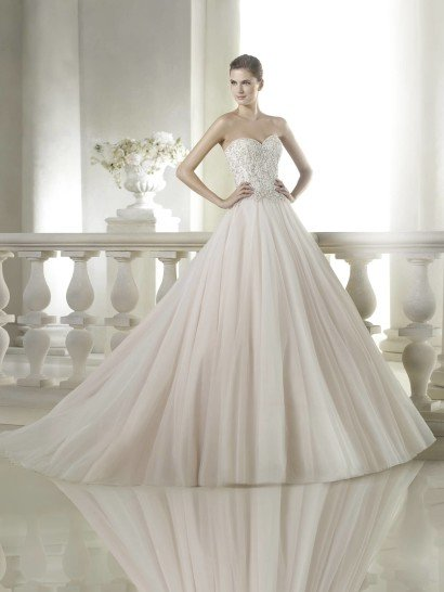 Открытое не белое свадебное платье создаст запоминающийся образ для торжественной церемонии.  Верх платья с декольте «сердечком» полностью расшит сияющими стразами и серебристой нитью.  На спинке к декору добавляются и декоративные пуговицы.  В сочетании с привлекательностью открытых рук и плеч такая отделка производит потрясающее впечатление.  Объемная матовая юбка без декора идеально его оттеняет.  Отсутствие на ней отделки совсем не кажется скучным благодаря длинному шлейфу.  Свадебное платье из коллекции San Patrick