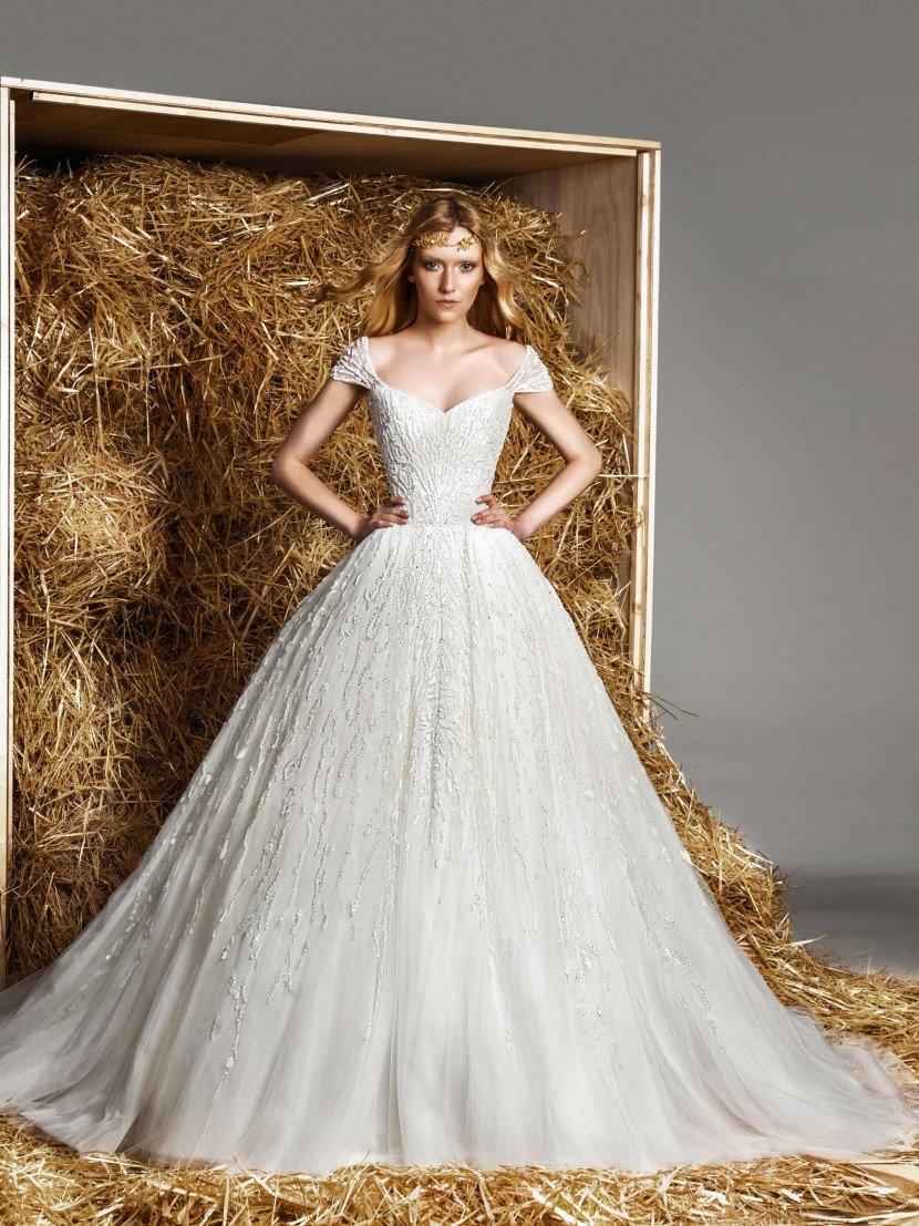 Пышное свадебное платье с портретным декольте и роскошным шлейфом.