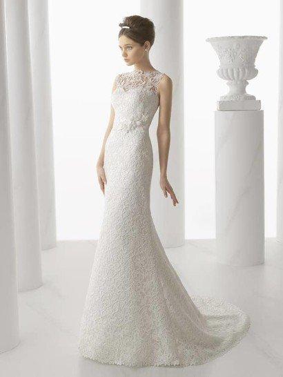 Свадебное платье с прямым силуэтом привлекает внимание своей богатой текстурой.  Выразительное кружево с цветочным рисунком полностью покрывает платье от закрытого верха до шлейфа средней длины.  Декольте, полускрытое кружевной тканью, имеет форму сердечка.  В области талии образ оригинально дополняют объемные цветы из белой ткани, расположенные ассиметрично.  На спине, под рядом декоративных пуговиц, начинается дополнительный шлейф из матового фатина.