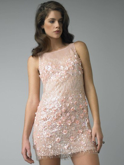 Коктейльное платье из нежной розовой ткани смотрится очень привлекательно благодаря прямому крою с американской проймой.  Такой верх подчеркивает красоту плеч и шеи.  Полупрозрачную ткань покрывает отделка из бисера и объемных розовых цветов, которые особенно плотно расположены на лифе и ниже линии талии.  Сочетание нежного декора и просвечивающей кожи делает платье одновременно соблазнительным и романтичным.