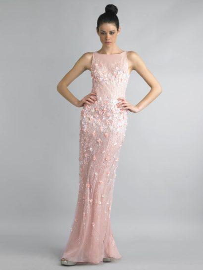 Нежное вечернее платье пудрово-розового оттенка прекрасно подчеркивает фигуру благодаря прямому силуэту и американской пройме.  Такая форма верха позволяет продемонстрировать плечи и руки, а слегка просвечивающая ткань делает образ еще более трогательным и романтичным.  Отделкой платья служат объемные цветы из розовой ткани и сияющая вышивка бисером и пайетками, которые сконцентрированы в области лифа и бедер.