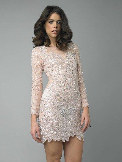 Короткое коктейльное платье пудрового розового оттенка почти сливается с тоном кожи, создавая соблазнительный эффект прозрачности. Юбка мини уравновешивается скромным верхом с длинными рукавами и вырезом лодочкой в элегантном, хоть и смелом образе.  У платья фигурный низ и роскошная отделка стразами и пайетками, которые плотно покрывают почти всю ткань, образуя силуэт с акцентом на тонкую талию и декольте в виде сердца.
