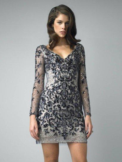 Коктейльное платье с выразительной отделкой привлечет все взгляды окружающих на торжественном мероприятии. V-образный вырез декольте повторяется и на спинке платья и делает образ элегантным, подчеркивает впечатление длинный рукав из прозрачной ткани дымчатого голубого оттенка.  Платье полностью расшито черными и голубыми пайетками, которые создают богатую текстуру в свете электрических огней.