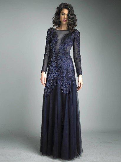 Вечернее платье глубокого темно-синего цвета красиво облегает фигуру благодаря прямому силуэту.  Верх платья выполнен из полупрозрачного материала, расшитого блестящими пайетками в тон ткани.  И длинный рукав, и область декольте смотрятся благодаря иллюзии прозрачности очень соблазнительно.  Низ выполнен из нескольких слоев более плотной ткани и красиво струится к самому полу от талии, полностью расшитой пайетками.  В салоне есть платья больших размеров.