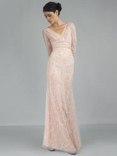 Романтичное вечернее платье в стиле ампир лаконично обрисовывает фигуру, не облегая ее.  Завышенная линия талии подчеркивает хрупкость силуэта, и отделка драпировками и бисером только поддерживает впечатление. Небольшой V-образный вырез красиво демонстрирует шею.  Прямая юбка из многослойной ткани украшена абстрактным узором вышивки и крупными стразами.  В сочетании с таким кроем нежный розовый оттенок материала делает образ очень свежим и трогательным.  Купите это платьедля встречи НовогоГода!
