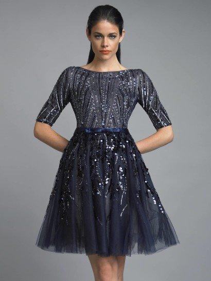 Короткое вечернее платье с юбкой А-силуэта в чернильно-синем цвете.  Закрытое декольте и рукав средней длины из непрозрачной ткани не кажутся слишком лаконичными благодаря роскошной отделке из пайеток синего цвета.  Талию подчеркивает небольшой атласный пояс.  От него начинается объемная многослойная юбка на бежевом чехле, выполненная из полупрозрачной темно-синей ткани, расшитой крупными пайетками и бисером.