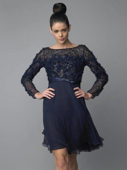 Коктейльное платье насыщенного чернильно-синего оттенка мягко очерчивает фигуру струящейся тканью. Чуть завышенная линия талии отделяет верх из полупрозрачной ткани от гладкой воздушной юбки с волнистым краем.  Верх платья с вырезом лодочкой и длинным рукавом отделан сияющей нитью и объемными цветами из ткани, которые смотрятся необычно и нежно в сочетании с небольшими блестящими пайетками.