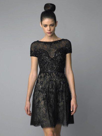 Коктейльное платье смотрится роскошно благодаря сочетанию изысканного кроя и пышной отделки. Широкий вырез бато подчеркивает шею, а небольшой рукав позволяет продемонстрировать руки. Юбка А-силуэта удачно смотрится на самых разных типах фигуры.  Кружевной слой ткани, использованный в качестве верха, расшит черным бисером по всей длине. Особенно выразительна отделка у воротника, на краях рукавов и в области лифа. Завершает образ тонкий атласный пояс.