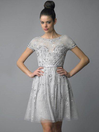 Элегантное коктейльное платье с закрытым верхом создает очень привлекательные очертания фигуры благодаря облегающему крою лифа и короткой юбке А-силуэта. Светлый серебристый оттенок ткани делает образ уместным на любом мероприятии.  Отделка выполнена серебристыми пайетками, абстрактный узор сконцентрирован на области декольте. Тонкую талию подчеркивает узкий глянцевый пояс с ассиметричным акцентом.