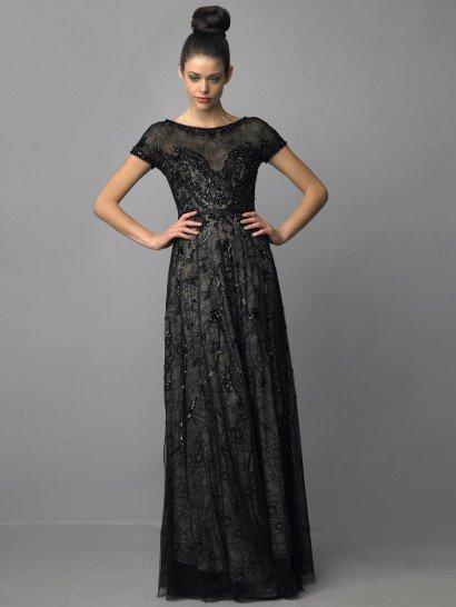 Шикарное вечернее платье черного цвета с вырезом бато и небольшим рукавом создает особенное настроение. Легкий блеск вышивки и полупрозрачность ткани смотрятся загадочно и привлекательно.  Талию выделяет узкий пояс из черного атласа. Его гладкая текстура отлично сочетается с кружевным узором верхнего слоя ткани платья. Бежевый материал основы позволяет выделить красоту кружева и сделать платье выразительнее.