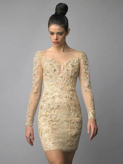 Роскошное коктейльное платье золотого цвета не останется незамеченным.  На полупрозрачной ткани, образующей длинные рукава и закрытое декольте, выполнена отделка тесьмой и стразами.  Плотный рисунок покрывает и лиф, и юбку платья.  Облегающий силуэт позволяет продемонстрировать все достоинства стройной фигуры и делает платье еще роскошнее, а глубокий вырез на спине делает образ особенно ярким.