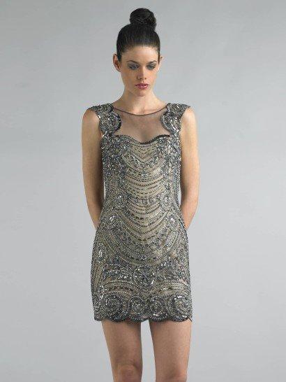 Короткое вечернее платье серого цвета сочетает в себе прямой крой и роскошную отделку. Юбка длиной до середины бедра выполнена с фигурным краем, что смотрится очень женственно и привлекательно. Декольте скрыто полупрозрачной тканью, а плечи украшают широкие бретели. Спинка платья демонстрирует глубокий вырез, оформленный так же, как и декольте.  Все платье расшито серебристыми пайетками. Подобная отделка будет особенно удачно смотреться в лучах электрических ламп.