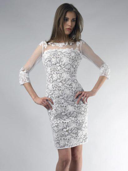 Коктейльное платье длиной до середины бедра привлекает внимание оригинальной кружевной отделкой.  Белый цвет подходит к любому типу внешности и делает образ уместным на самых разных мероприятиях.  Манжеты длинных рукавов и вырез бато отделаны кружевными аппликациями на полупрозрачной ткани.  С линии лифа начинается кружевная отделка с таким же узором, полностью покрывающая платье до самого низа.  Благодаря гармонично подобранному оттенку основы, кружево выглядит объемным и роскошным.