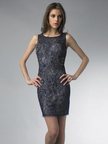 Коктейльное платье соблазнительно облегает фигуру до середины бедра.  Основой служит бежевый чехол с открытым декольте в форме сердца, а верхний, темно-синий слой ткани формирует закрытый верх с вырезом под горло и двумя широкими бретелями.  Кружевная ткань верха расшита бисером. Цветочный узор вышивки хорошо сочетается с мотивом кружева и делает платье особенно выразительным в лучах света.