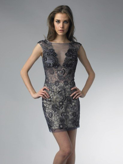 Коктейльное платье темно-синего цвета выполнено из полупрозрачной ткани на бежевом чехле, отчего смотрится очень смело и соблазнительно. Верх выглядит элегантно благодаря классической форме выреза-лодочки и небольшому рукаву, скрывающему плечи.  Платье отделано вышивкой из бисера, которая плотнее всего сконцентрирована на лифе и в области плеч. В сочетании с прозрачностью ткани крупный узор отделки выглядит еще привлекательнее.