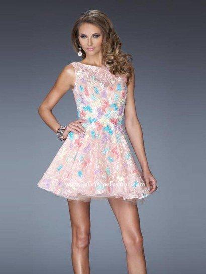 Необычное короткое вечернее платье с разноцветной отделкой никого не оставит равнодушным. Пышная юбка А-силуэта выделяет женственные изгибы, а вырез лодочкой подчеркивает элегантность фигуры.  Цветные аппликации из кружева пастельных тонов прекрасно вписываются в светлый розовый оттенок ажурной ткани, из которой выполнено вечернее платье.  Дополнительным украшением образа служит глубокий вырез на спине, полускрытый прозрачным материалом.