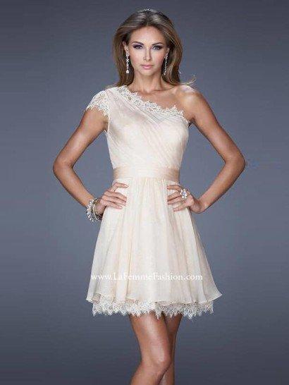 Элегантное короткое вечернее платье молочно-бежевого оттенка запоминается своим ассиметричным кроем. Лиф с одной широкой бретелью сочетается с прямым силуэтом с подчеркнутой атласным поясом талией.  Мягкое сияние ткани само по себе выглядит привлекательно, но кружево, декорирующее верх и подол юбки, привносит в образ особое очарование.