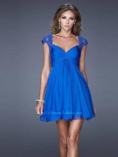 Красивое короткое вечернее платье покоряет, в первую очередь, сияющим оттенком синего. Кроме того, невероятно женственный крой преображает фигуру благодаря рукавам-крылышкам, прямому силуэту и соблазнительному лифу с драпировками ткани.  Декором служит полупрозрачная ткань с кружевными аппликациями, расшитая бисером, из которой выполнены короткие рукава вечернего платья.