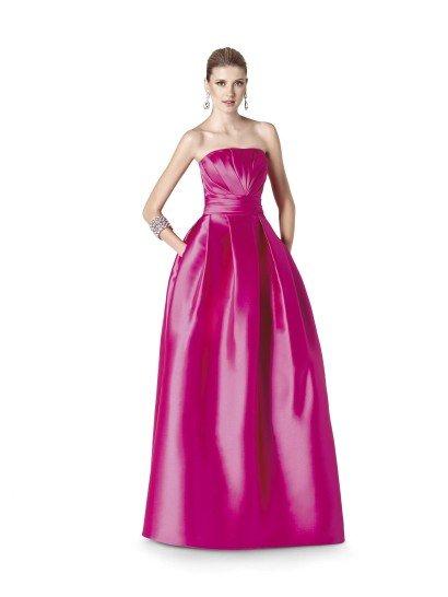 Роскошное вечернее платье из плотного, глянцевого атласа смелого цвета фуксии – выбор для решительных и уверенных в себе девушек. Открытый верх с драпировками ткани позволяет соблазнительно продемонстрировать декольте, а на поясе драпировки подчеркивают изящность фигуры.  Пышная юбка красива лаконичностью своего кроя, кроме того, она выделяется оригинальной деталью – расположенными по бокам скрытыми карманами.  Вечернее платье 2015 года из коллекции It's My Party/ Pronovias Fashion Group /