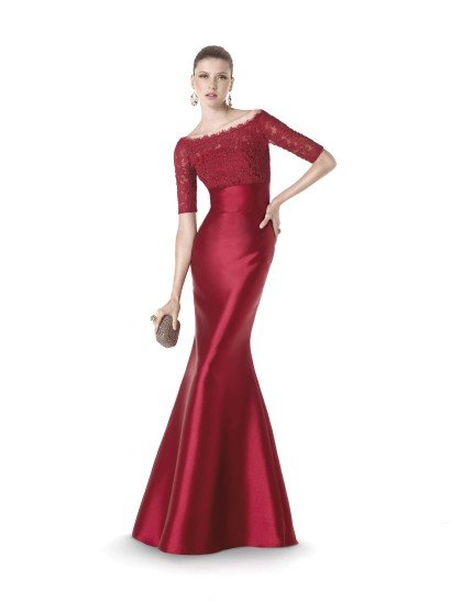 Красивое вечернее платье, смело сочетающее в себе текстуры гладкого атласа и нежного кружева с цветочным рисунком. Впечатление дополняет глубокий красный оттенок ткани, полный женственной чувственности.  Широкий пояс и рукав длиной до локтя подчеркивают изящный силуэт, создаваемый прямым кроем вечернего платья. Ажурный край декольте становится завершающей деталью, позволяющей использовать образ без всяких дополнений.  Вечернее платье 2015 года из коллекции It's My Party/ Pronovias Fashion Group /