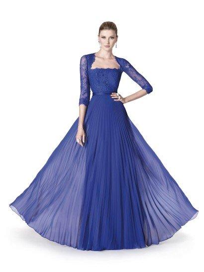 Яркое вечернее платье на свадьбу василькового синего цвета красиво струится, очерчивая фигуру, при каждом движении.  Крой декольте с ажурной отделкой акцентирует внимание на форме шеи и плеч, а рукав длиной в три четверти выгодно демонстрирует руки.  Подчеркивает хрупкий силуэт небольшой атласный пояс.  Многослойная плиссированная юбка выглядит романтичной и легкой благодаря полупрозрачности верхнего слоя ткани