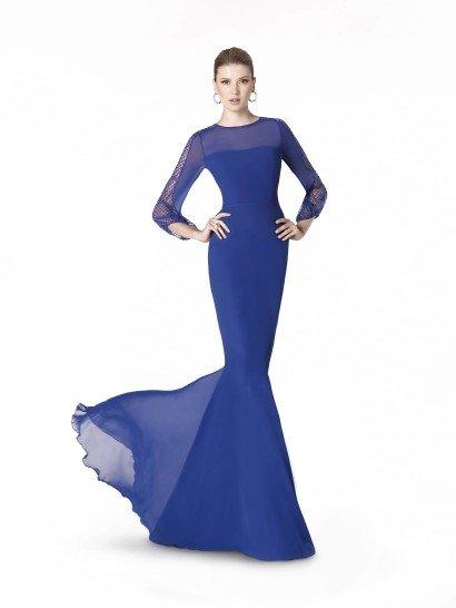 Закрытое вечернее платье насыщенного синего оттенка сочетает сдержанную элегантность длинных рукавов и соблазнительную женственность облегающего кроя «русалка». Оригинальную ноту привносят сетчатые вставки по всей длине рукава.  Под полупрозрачной тканью угадывается красивая линия прямого декольте, а талию обозначает узкий пояс. Строгость линий и декора позволяют дополнять образ любыми аксессуарами.  Вечернее платье 2015 года из коллекции It's My Party/ Pronovias Fashion Group /