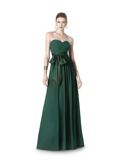 Открытое вечернее платье выразительного зеленого оттенка подойдет тем, кто любит делать яркие акценты в образе.  Декольте в форме «сердца» с драпировками ткани и длинная юбка прямого кроя служат отличным обрамлением для роскошного пояса с крупным ассиметрично расположенным бантом.  Контраст глянцевой и матовой тканей служит достаточным украшением, поэтому лаконичное вечернее платье не дополнено другой отделкой.  Вечернее платье из коллекции It's My Party/ Pronovias Fashion Group /