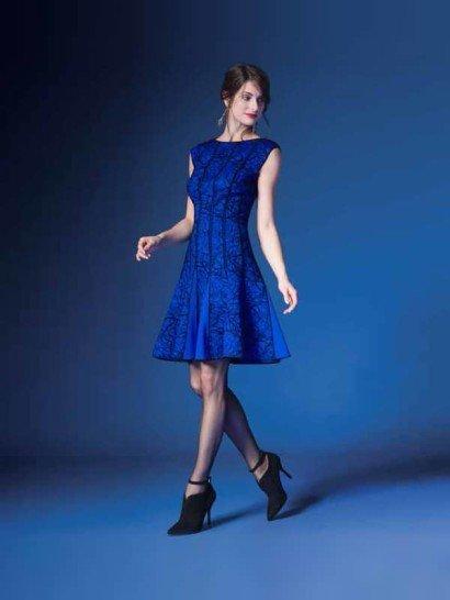 Вечернее платье длиной до колена сочетает в себе экстравагантную отделку и оригинальный крой.   Юбка А-силуэта и вырез бато придают образу женственность, а графичные линии отделки делают его выразительнее.  Подол юбки декорирован вставками из однотонной синей ткани, совпадающей с одним из оттенков принта на вечернем платье.   Лаконичный черный узор позволяет дополнять образ другими тонами с помощью аксессуаров.