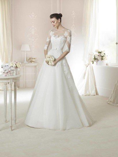 Закрытое свадебное платье, создающее легкий и женственный образ. Юбка А-силуэта в сочетании с небольшим поясом подчеркивают хрупкую фигуру невесты.  Полупрозрачная ткань верха с рукавом длиной три четверти настраивает на романтичный лад.  Отделка из кружевных аппликаций с белыми пайетками украшает верх свадебного платья.  Кроме того, верхний слой фатина на юбке, как и материал рукавов, имеет оригинальную текстуру с мелким геометрическим рисунком.