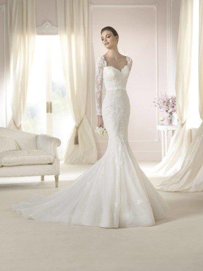 Элегантное недорогоесвадебное платье для романтичной невесты.  Силуэт «русалка» облегает фигуру, пышная от линии коленей юбка сзади заканчивается шлейфом.  Небольшой пояс делает акцент на стройной талии невесты.  Декольте в форме сердечка и весь верх свадебного платья декорированы кружевом, из ажурной ткани выполнены и длинные рукава.  Небольшие аппликации из кружев украшают юбку, а ее край отделан широкой декоративной лентой.