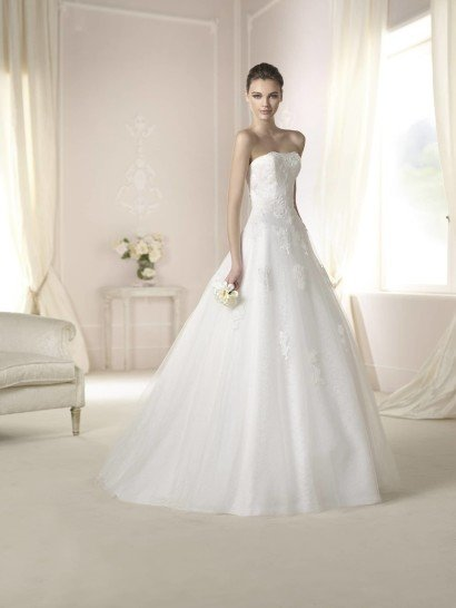 Открытое свадебное платье 2015 с прямым декольте смотрится соблазнительно и торжественно. А-силуэт с небольшим шлейфом сзади придает очертаниям фигуры особенную женственность, и открытые плечи подчеркивают это впечатление.  Свадебное платье отделано объемным кружевом, которое плотно покрывает лиф и аппликациями расположено на юбке. Кроме того, верхний слой тюльмарина на юбке выполнен с нежным рисунком.