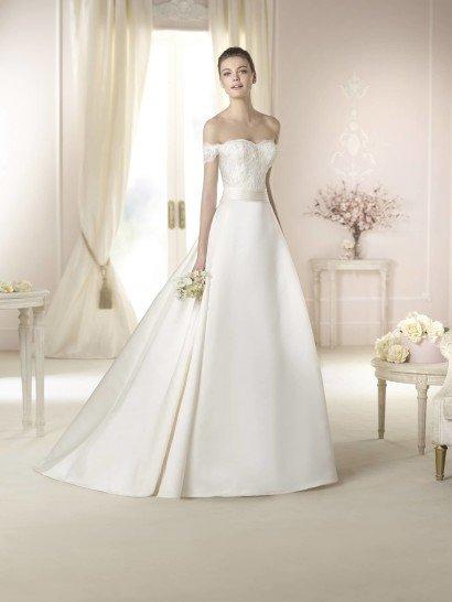 Открытое свадебное платье запоминается своей скульптурной четкостью линий.  Открытый лиф женственной формы с заниженным кружевным рукавом декорирован кружевом, спускающимся до линии талии.  Ее выделяет атласный пояс, красиво контрастирующий с текстурой ажурного верха.  Юбка из матового атласа спускается к полу такими выразительными волнами, что не нуждается ни в каких дополнительных элементах кроя кроме шлейфа средней длины.